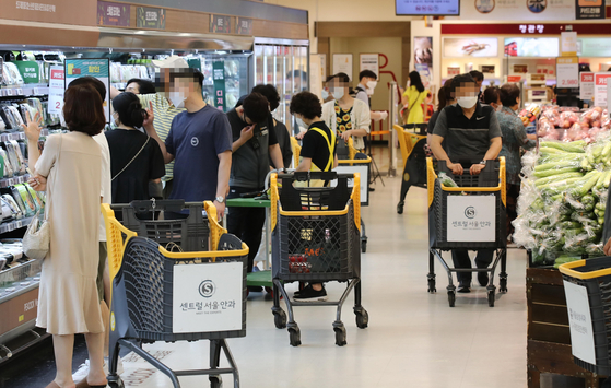 Shoppers crowd a discount supermarket's aisles on Sunday. According to major retailers including Emart, food and beverage sales have gone up between 4 and 7 percent compared to the previous week as more people stay home due to tightened social distancing regulations. [YONHAP]