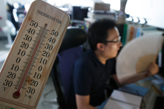 In this file photo, a government worker uses a fan as the air conditioning system of the government complex in central Seoul is shut down to prevent a blackout on Aug. 13, 2013. The room temperature was 34 degree Celsius without air conditioning.  [NEWS1]