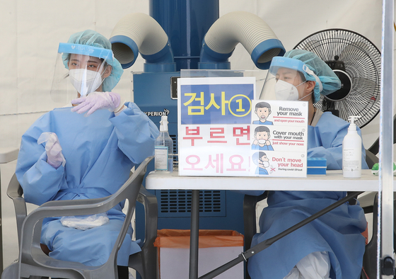 Medical workers get ready to carry out Covid-19 tests at a Covid-19 testing site in Nowon District, northern Seoul, on Sunday. [NEWS1]