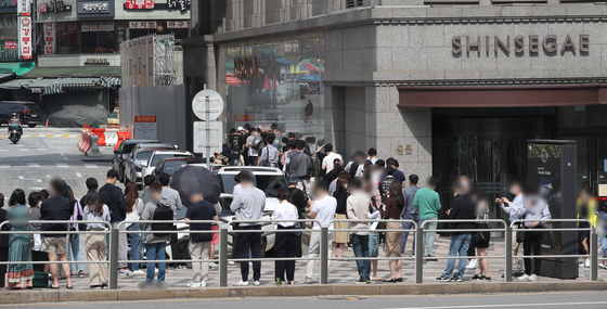 Customers wait in a long line in front of Shinsegae Department Store in Jung District, central Seoul, on May 29. [YONHAP]