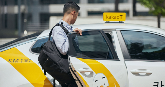 A passenger gets in a Kakao Blue taxi. [KAKAO MOBILITY]