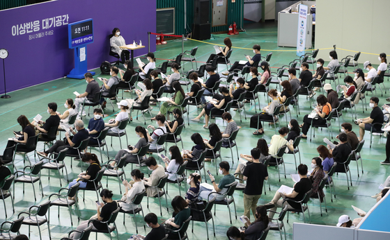 A vaccination center in Bucheon, Gyeonggi, is crowded with people waiting to get a shot on Monday, as health authorities started a program to inoculate high school seniors and faculty members at 290 vaccination centers across the country. [YONHAP]