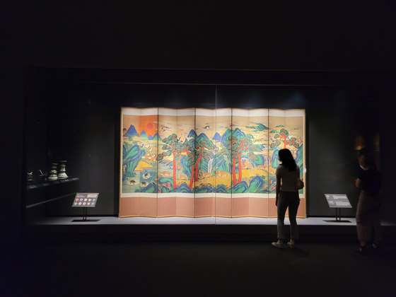 """Visitors to the exhibition look at """"Ten-panel Folding Screen with the Ten Longevity Symbols""""(19th century) from the Joseon period.[MOON SO-YOUNG]"""