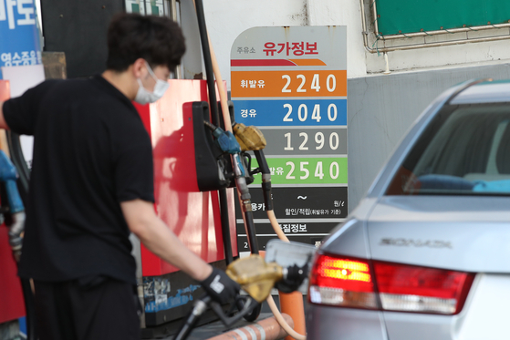 A car owner pumps gas into his car. [NEWS1]