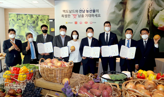 South Jeolla Governor Kim Yung-rok, fourth from right, and McDonald's Korea Managing Director Antoni Martinez, third from right, pose for a photo after signing a memorandum of understanding (MOU) on Tuesday. The fast food franchise will receive ingredients locally sourced from South Jeolla farmers to make its burgers. [MCDONALD'S KOREA]