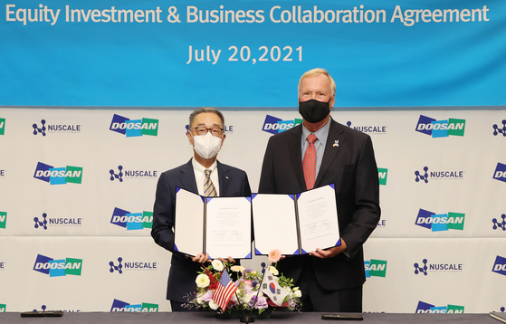 Doosan Heavy Industries & Construction Chairman and CEO Park Gee-won, left, Chairman and NuScale Power Chairman and Chief Executive Officer John Hopkins pose during a signing ceremony at the company's office in Bundang, Gyeonggi, on Tuesday. [DOOSAN HEAVY INDUSTRIES&CONSTRUCTION]