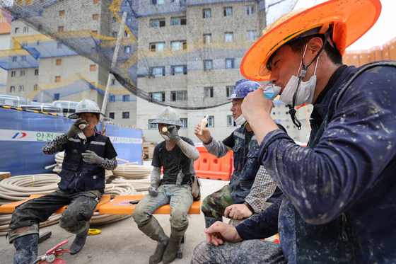 Workers take a break while enjoying popsicles under a shade at an SK apartment construction site in Incheon on Tuesday. Officials overseeing the construction say that they have taken steps to help workers beat the heat, including installing cooling systems and taking turns having breaks. [YONHAP]