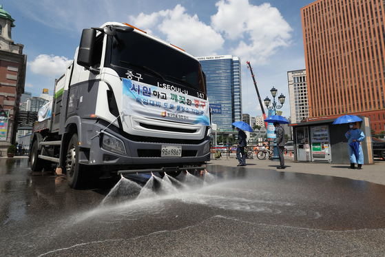Water trucks spray a street near Seoul Station to cool it off as temperatures exceeded 36 degrees Celsius (96.8 Fahrenheit) in Seoul on Wednesday.  [NEWS1]
