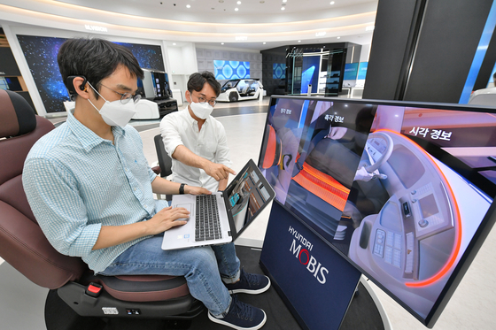 Researchers at Hyundai Mobis try out the M.Brain technology which detects brainwave and warns the driver. [HYUNDAI MOBIS]