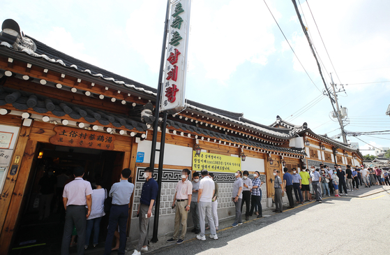 People line up in front of a restaurant in central Seoul to eat samgyetang, or chicken soup with ginseng, on Wednesday in time for Jungbok, which marks the midpoint of the hottest period of the summer. [YONHAP]