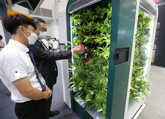 A visitor takes a look at plant-based air purifier Airim developed by Biocraft at the Korea International Cooling Industry Expo held in Daegu on Wednesday. The expo, which runs through July 23, is dedicated to displaying various products that can counter climate change and improve air quality. [YONHAP]