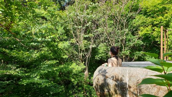 A visitor enjoys the view of the forest surrounding a stone jacuzzi at Restree Resom, a newly opened resort in Jecheon, North Chungcheong. [LIETTO]