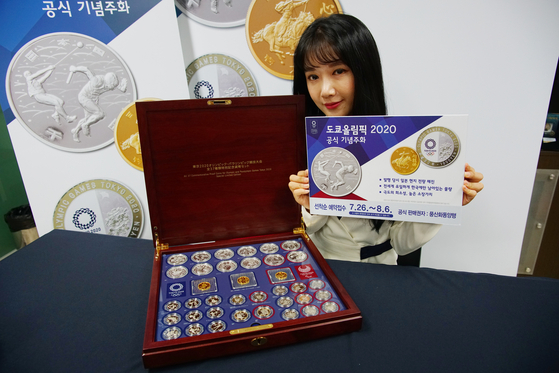 A model holds up coins commemorating the 2020 Tokyo Olympics, which officially starts on Friday. The coins are sold by Poongsan Hwadong. The Tokyo Olympics was postponed by a year due to the Covid-19 pandemic, the first Games ever to be delayed. Poongsan Hwadong has been selling the commemorative coins since the 1952 Helsinki Games. [POONGSAN HWADONG]