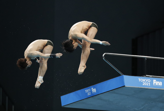 Kim Yeong-nam, left, and Woo Ha-ram in action during the men's synchronised 10-meter platform final at the FINA Diving World Cup 2021 at the Tokyo Aquatics Centre, Tokyo on May 1. [YONHAP]
