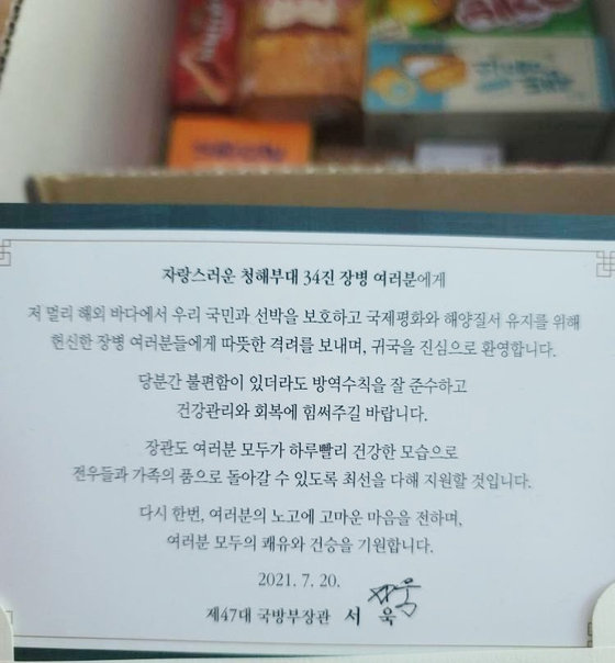 In this photo, a box of snacks sent by Defense Minister Suh Wook to a Covid-19-infected member of the Cheonghae Unit is seen with a letter.  [Provided by the Cheonghae Unit sailor]