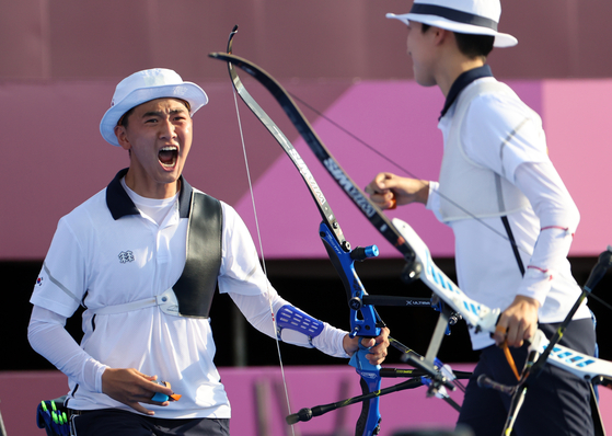 The Korean mixed team archers Kim Je-deok, left, and An San celebrate after winning gold in the mixed team archery event at the 2020 Tokyo Games at Yumenoshima Park Archery Field in Tokyo on Saturday. [YONHAP]
