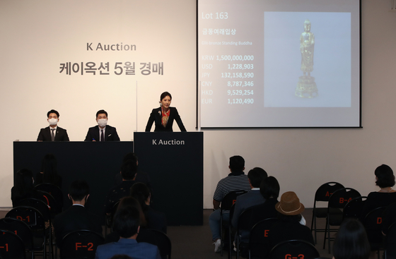 An auctioneer welcomes bids for Gilt-bronze Standing Bodhisattva at K Auction in southern Seoul last year. Kansong Art and Culture Foundation placed three art treasures up for auction last year, citing financial difficulties. [YONHAP]