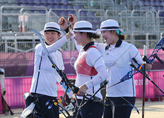 Jang Min-hee, An San and Kang Chae-young of the Korean women's archery team celebrate after winning the gold medal match in three straight sets against Russia on Sunday at Yumenoshima Park Archery Field in Tokyo. [JOINT PRESS CORPS]