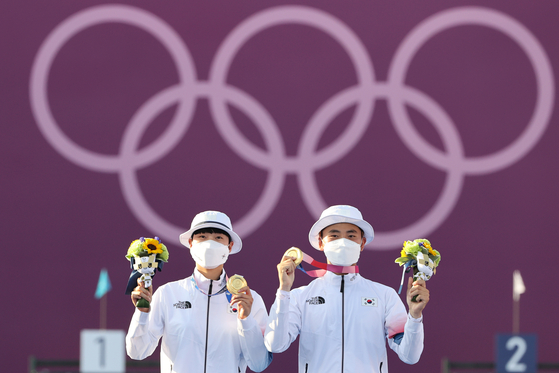 An San, left, and Kim Je-deok hold up their archery mixed team gold medals on the podium on Saturday at Yumenoshima Park Archery Field in Tokyo. [NEWS1]