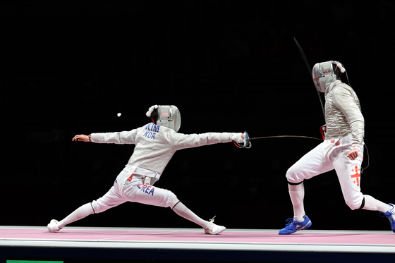 Kim Jung-hwan lunges toward Sandro Bazadze of Georgia in the men's sabre bronze medal match at Makuhari Messe Hall, Chiba, Japan on Saturday. [JOINT PRESS CORPS]