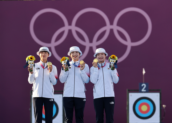 From left to right, An San, Jang Min-hee and Kang Chae-young of the Korean women's archery team hold up their gold medals after winning the final match against Russia in three straight sets on Sunday at Yumenoshima Park Archery Field in Tokyo. [JOINT PRESS CORPS]