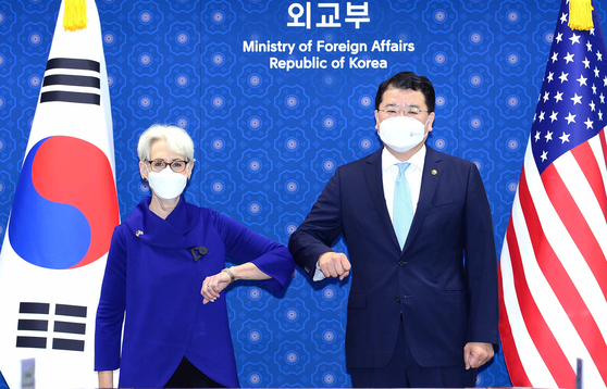 South Korean First Vice Foreign Minister Choi Jong-kun, right, and U.S. Deputy Secretary of State Wendy Sherman bump elbows ahead of talks at the Foreign Ministry in central Seoul, Friday. [FOREIGN MINISTRY]