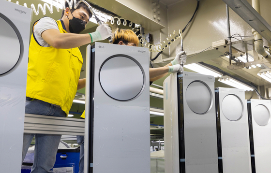 An employee assembles air conditioners at an LG Electronics factory in Changwon, South Gyeongsang. The company announced on Sunday that its production line is operating at full capacity amid high demand for air conditioners during the heat wave. [YONHAP]