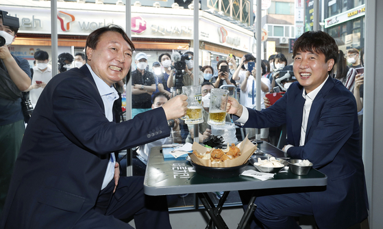 People Power Party Chairman Lee Jun-seok, right, and former Prosecutor General Yoon Seok-youl raise their glasses at a bar in Seoul on Sunday. [NEWS1]