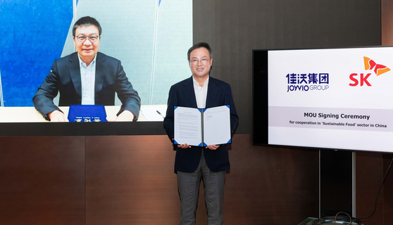 SK Inc. CEO Jang Dong-hyun poses after signing an agreement with his counterpart from China's Joyvio to create a 100-billion-won fund on Monday in central Seoul. [SK INC.]