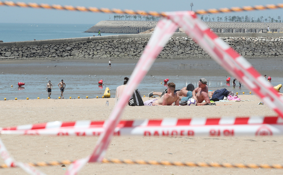 Tourists sit maskless in the sand behind the control line at Eurwangni Beach in Incheon on Sunday, despite the temporary closure of four major beaches in Incheon, including Eurwangni, Wangsan, Hanagae and Silmi, following the Level 4 measures applied in the region. Incheon temporarily closed beaches in Jung District until July 25 and banned the use of shower rooms, parasols, tents and rental facilities. [NEWS1]