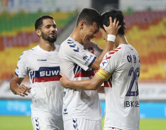 Lee young-jae of Suwon FC, middle, celebrate with his teammates after scoring a winning goal against the Suwon Samsung Bluewings at the Suwon World Cup Stadium in Suwon, Gyeonggi on Tuesday. [ILGAN SPORTS]