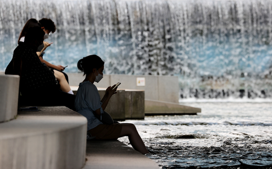 People cool themselves off under a bridge at the Cheonggyecheon, a restored stream that runs through in Jongno District, central Seoul, on Tuesday, as the scorching heat prevails. [YONHAP]
