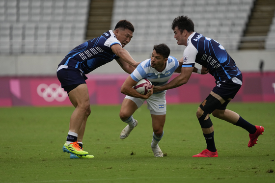 Argentina's Lautaro Bazan Velez, center, is challenged by Korea's Han Kun-kyu, left, and Coquillard Andre Jin in their men's rugby sevens match on Tuesday in Tokyo. [AP/YONHAP]