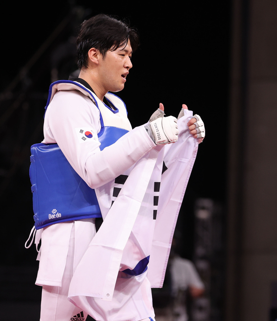 In kyo-don raises both thumbs up towards his coach after winning his bronze medal. [YONHAP]