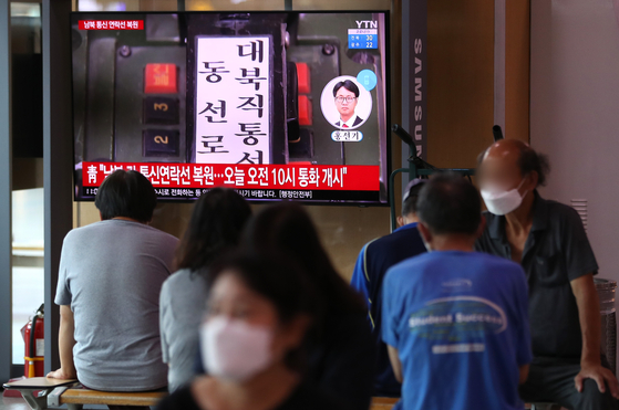 South Koreans at Seoul Station Tuesday morning watch on the news that Seoul and Pyongyang decided to restore inter-Korean communication lines. [NEWS1]