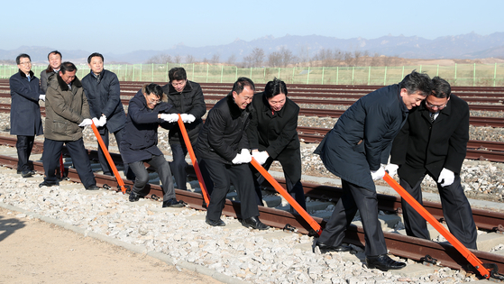 South and North Korean officials connect the rails between the two Koreas at Panmun Station in Kaesong at a symbolic groundbreaking ceremony on Dec. 26, 2018 to begin a project to reconnect their roads and railways. [JOINT PRESS CORPS]