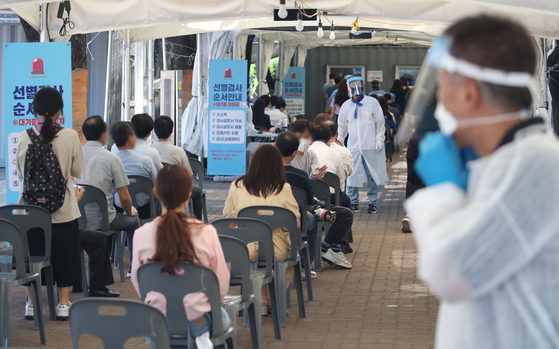 People wait in line to receive Covid-19 tests at a makeshift testing clinic in Yeongdeungpo District, western Seoul on Monday. [YONHAP]