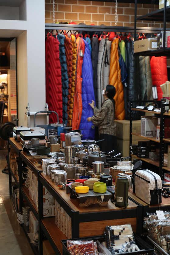 A shopper looks at camping equipment displayed at Play Monkey, a camping supply store in Yeongdeungpo District, western Seoul, on Wednesday. According to Lotte Mart, sales of camping gear between July 1 and 26 rose 36.8 percent on year as many chose to go camping instead of visiting crowded vacation spots during the pandemic. [YONHAP]