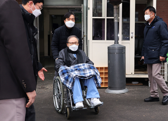 In this file photo, former President Lee Myung-bak, in a wheelchair, leaves Seoul National University Hospital on Feb. 10 to return to Anyang Correctional Institution after two-months of medical treatment. [YONHAP]