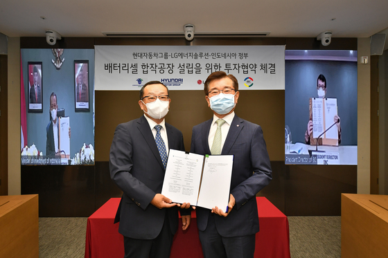Cho Sung-hwan, CEO of Hyundai Mobis, left, and Kim Jong-hyun, CEO of LG Energy Solution, pose for a photo after signing a memorandum of understanding in Seoul on Thursday. Bahlil Lahadalia, left in the back, Investment Minister of Indonesia, and Toto Nugroho, right in the back, CEO of Indonesia Battery Corporation joined the event virtually. [HYUNDAI MOTOR]