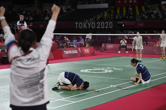Kong Hee-yong (center) and Kim So-yeong (right) celebrate as their coach cheers after winning their women's doubles badminton quarterfinal. [AFP/YONHAP]