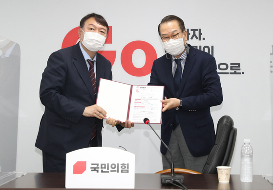 Former Prosecutor General Yoon Seok-youl, left, a conservative presidential candidate, submits his application to join the main opposition People Power Party (PPP) to Rep. Kwon Young-se, chief of the party's external relations committee, at the PPP headquarters in Yeouido, western Seoul, Friday. [NEWS1]