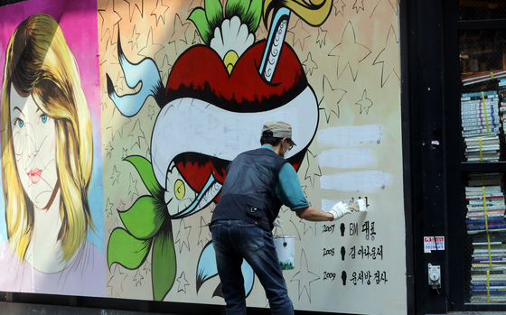 """A mural entitled """"Julie's men"""" painted on a bookstore wall in Jongno District, central Seoul, seen to be disparaging former Prosecutor General Yoon Seok-youl's wife, has been receiving backlash from Yoon's supporters. A man covers up the list of high-profile men she has been rumored involved with in the past with white paint Friday. [NEWS1]"""
