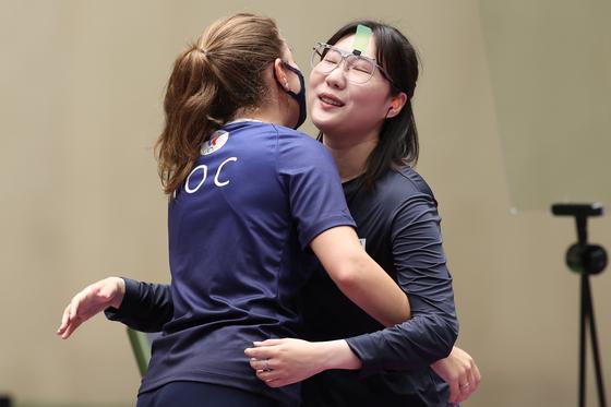 Vitalina Batsarashkina (left) and Kim Min-jung hug after the women's 25-meter pistol final during the shooting event at the 2020 Olympic at Asaka Shooting Range on Friday. [TASS/YONHAP]