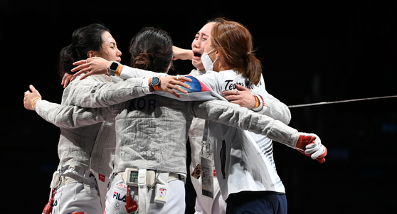 From left: Kim Ji-yeon, Seo Ji-yeon, Yoon Ji-su and Choi Soo-yeon celebrate after winning the women sabre team bronze medal at the Tokyo Olympics on Saturday at the Makuhari Messe Hall in Chiba, Japan. [JOINT PRESS CORPS]