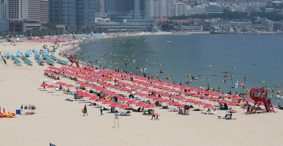 Beachgoers cool themselves off at Haeundae Beach in Busan on Sunday. Beaches are quieter this year as vacationers try to avoid popular places in the midst of the fourth wave of Covid-19 cases.  [SONG BONG-GEUN]