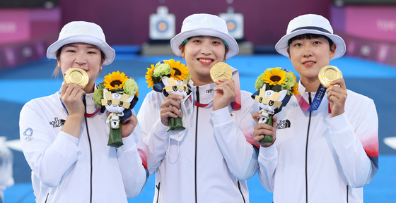 From left, Kang Chae-young, Jang Min-hee and An San of the Korean women's archery team celebrate after winning the gold medal match in three straight sets against Russia on July 25 at Yumenoshima Park Archery Field in Tokyo. [YONHAP]