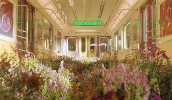 """NCT U's music video for """"Make A Wish (Birthday Song)"""" (2020) ends showing a butterfly fluttering through a subway car overgrown with flowers, a scene which reappears in the """"Black Mamba"""" music video released by aespa a month later. [SCREEN CAPTURE]"""