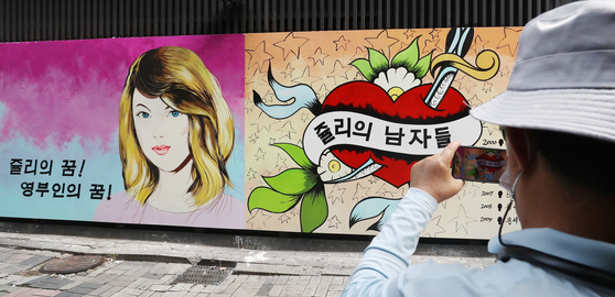 A photo of the wall paintings outside a bookstore in Jongno District, central Seoul, which refer to rumors that Yoon Seok-youl's wife worked as a hostess at a nightlife establishment under the alias of Julie. On the right, the caption says, ″Julie's dream! Becoming the first lady!″ On the left, the center of the red heart reads, ″Julie's men.″ [NEWS1]