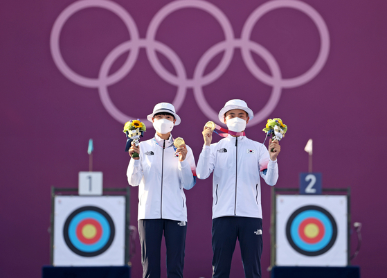 An San, left, and Kim Je-deok hold up their archery mixed team gold medals on the podium on July 24 at Yumenoshima Park Archery Field in Tokyo. [YONHAP]